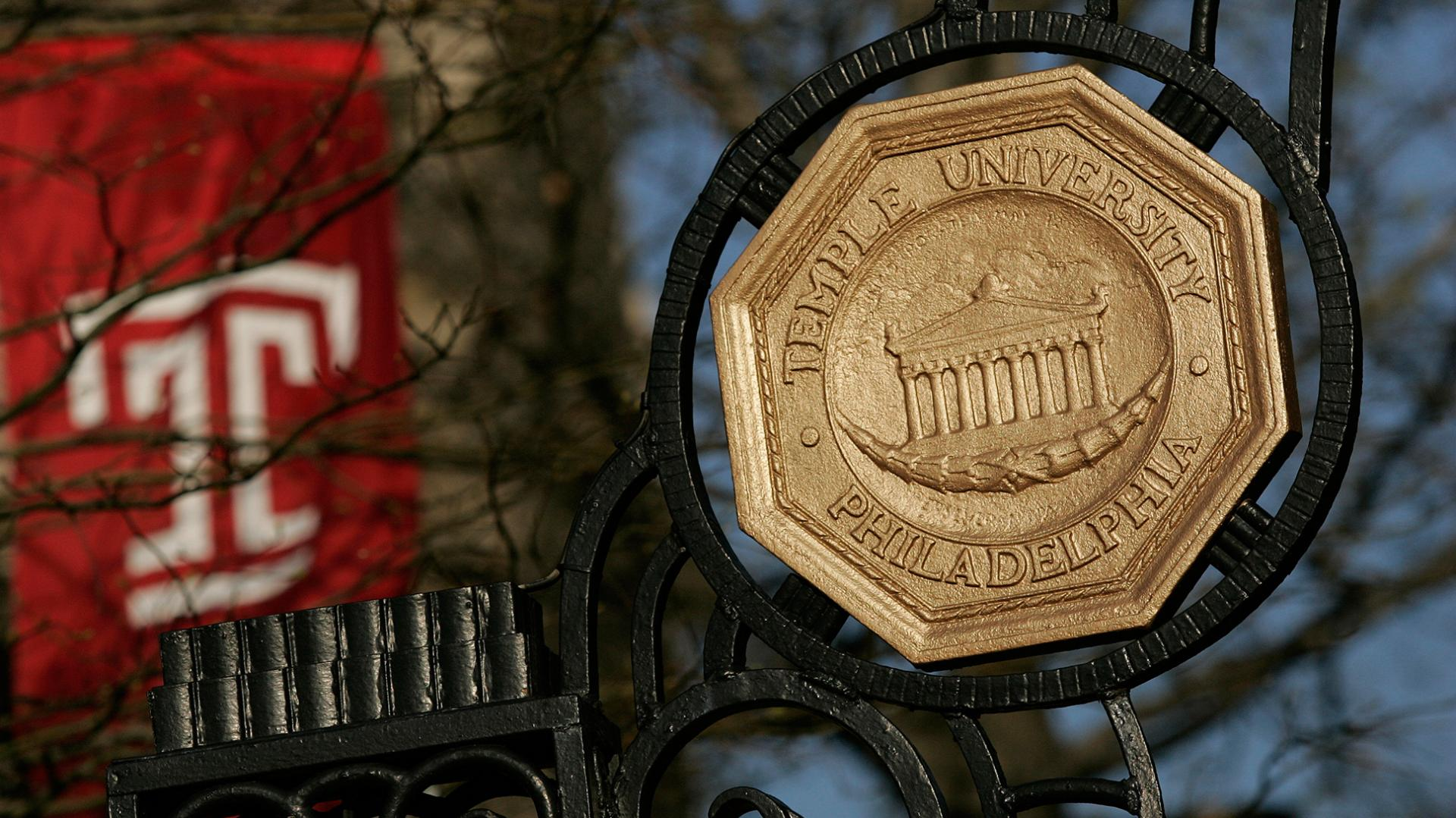 Temple University Seal in brass hangs on a gate as entrance to campus